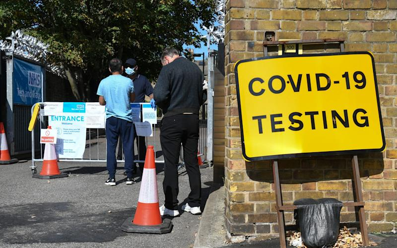 People queue up outside a coronavirus testing centre offering walk-in appointments in east London - PA/PA