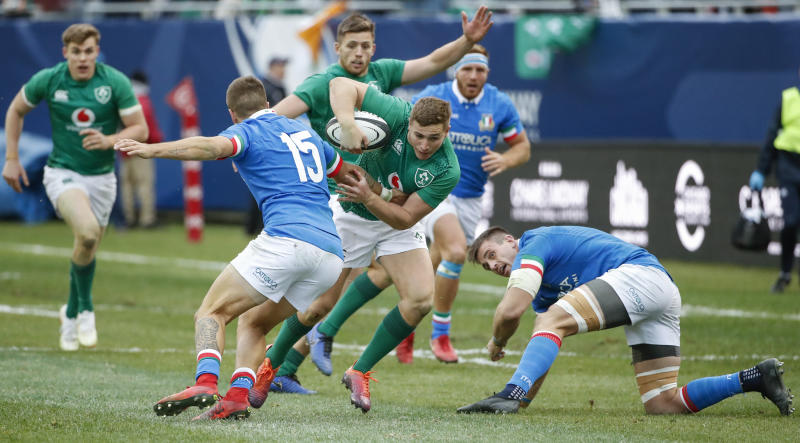 Ireland's Jordan Larmour, center, goes past Italy's Luca Sperandio, left, during the second half of rugby match Saturday, Nov. 3, 2018, in Chicago. (AP Photo/Kamil Krzaczynski)