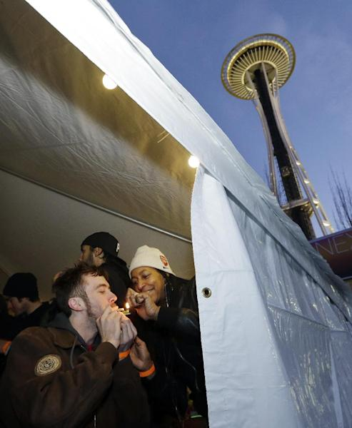 Rhonda Bell, right, and Austin Scott light up a marijuana joint at a pot party at the Seattle Center Friday, Dec. 6, 2013, in Seattle. Friday marked the first anniversary of the day Washington's legal marijuana law took effect, and hundreds of people celebrated by lighting up near the Space Needle at a party permitted by the city of Seattle. (AP Photo/Elaine Thompson)