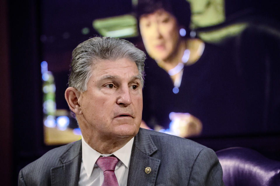 FILE - In this May 12, 2021, file photo, Sen. Joe Manchin, D-W.Va., listens as Sen. Susan Collins, R-Maine, on the monitor behind him, asks questions during a hearing on Capitol Hill in Washington. Senators labored Tuesday to find a path forward for legislation creating a commission on the Jan. 6 insurrection, debating potential changes in a long-shot attempt to overcome growing GOP opposition. Collins and Manchin are leading the informal talks, according to two people familiar with the effort. (Bill O'Leary/The Washington Post via AP, Pool)