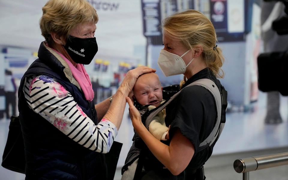 Susan Handfield meets her baby granddaughter Charlotta for the first time, held by her mother Eva as they arrive at Heathrow from Berlin - AP Photo/Matt Dunham