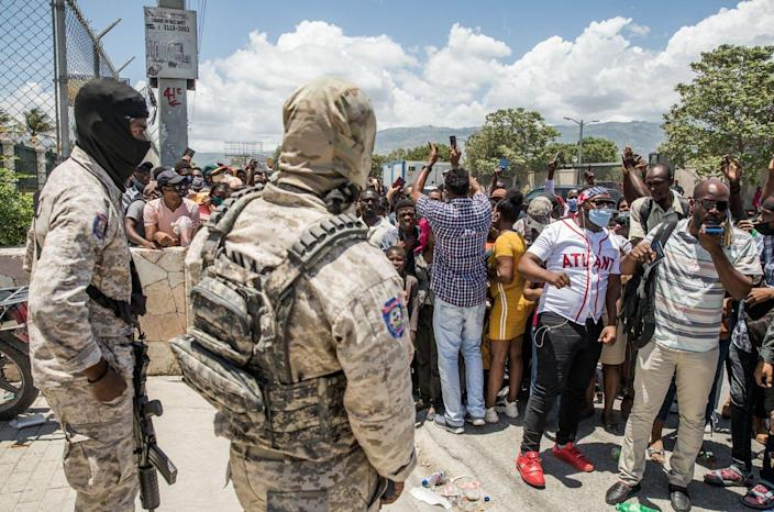"""<span class=""""caption"""">Haitians seeking asylum gather July 10, 2021, at the U.S. Embassy in Haiti after the president's assassination plunged the country further into chaos,</span> <span class=""""attribution""""><a class=""""link rapid-noclick-resp"""" href=""""https://www.gettyimages.com/detail/news-photo/police-look-on-as-haitian-citizens-gather-in-front-of-the-news-photo/1233910041"""" rel=""""nofollow noopener"""" target=""""_blank"""" data-ylk=""""slk:VALERIE BAERISWYL/AFP via Getty Images"""">VALERIE BAERISWYL/AFP via Getty Images</a></span>"""