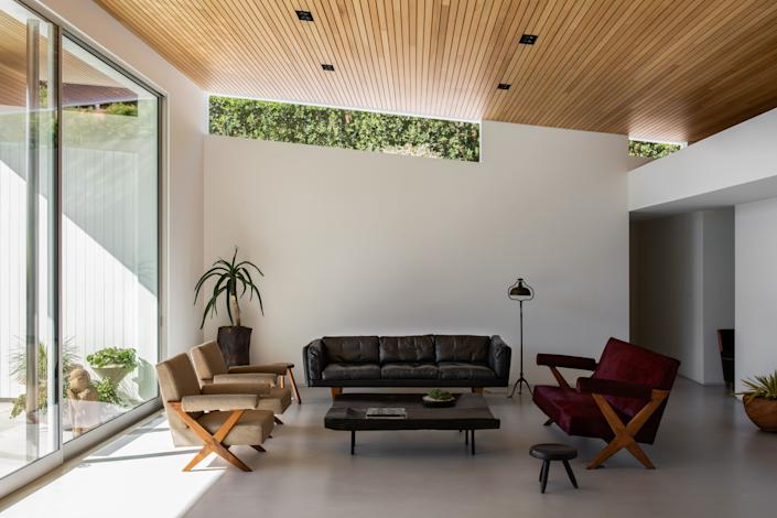 Statham and interior designer Courtney Applebaum opted for a minimalist look for the home's living room, to better highlight the clean lines of the space. The black leather couch is Illum Wikkelso, and the red couch and armchairs are by Pierre Jeanneret. The coffee table is a 1930s antique from Galerie Half.