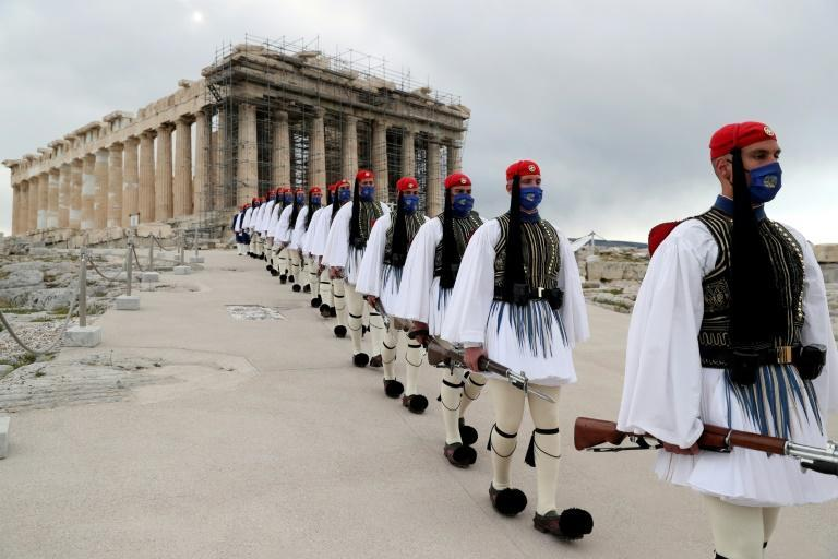 Members of the Presidential Guard walked in front of the Parthenon temple atop of Acropolis Hill after the Greek flag raising ceremony