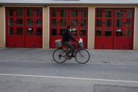 A man wears a face mask on his bicycle in central capital Nicosia, Cyprus, Wednesday, Jan. 27, 2021. Cyprus' health minister Constantinos Ioannou said that the first to re-open as of Feb. 1st will be hair and beauty salons followed a week later by retail stores, shopping malls and elementary schools. Students in their final year of high school will also go back to classes on Feb. 8. (AP Photo/Petros Karadjias)