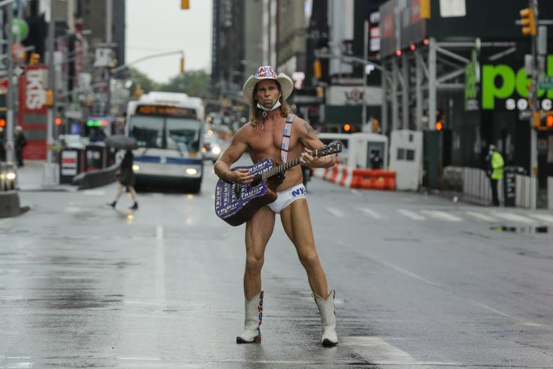 Robert Burck, who performs as the Naked Cowboy, poses for photographs in Times Square during the coronavirus pandemic , Saturday, May 23, 2020, in New York. (AP Photo/Frank Franklin II)