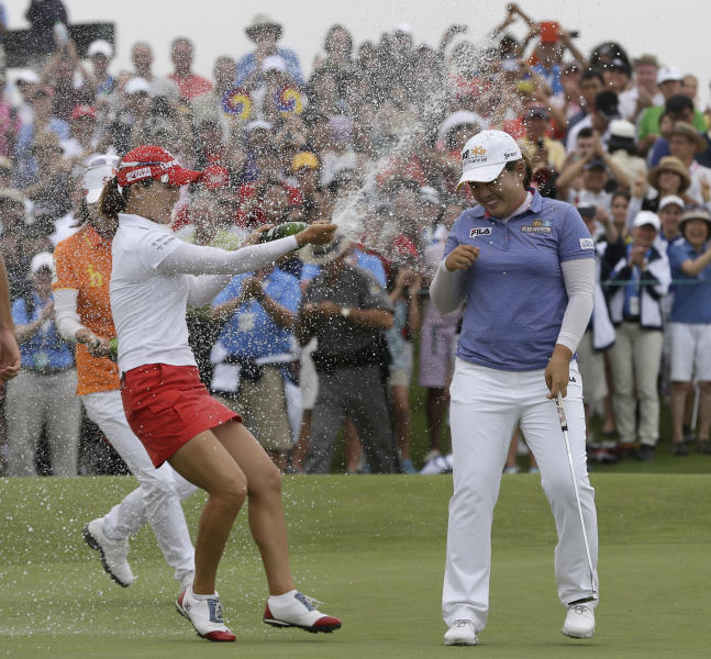 Inbee Park, of South Korea, is sprayed with champagne after sinking her last putt on the 18th green during the final round at the U.S. Women's Open golf tournament at Sebonack Golf Club in Southampton, N.Y., Sunday, June 30, 2013. Inbee Kim won the championship, shooting 8 under-par. (AP Photo/Seth Wenig)