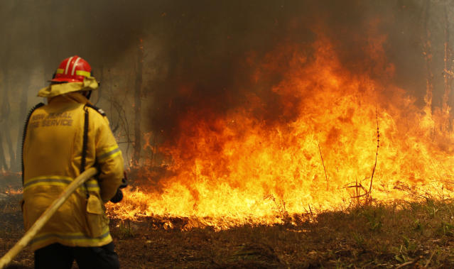 Firefighters work to contain a bushfire along Old Bar road in Old Bar, Saturday, Nov. 9, 2019. Wildfires razing Australia's drought-stricken east coast have left two people dead and several missing, more than 30 injured and over 150 homes destroyed, officials said Saturday.(Darren Pateman/AAP Image via AP)