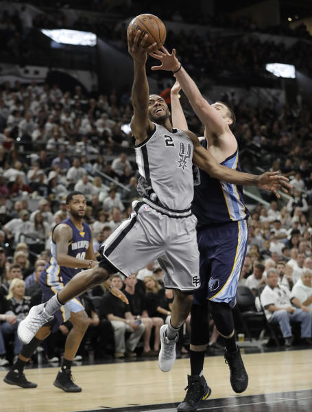 San Antonio Spurs forward Kawhi Leonard (2) drives to the basket past Memphis Grizzlies center Marc Gasol (33) during the second half in Game 1 of a first-round NBA basketball playoff series, Saturday, April 15, 2017, in San Antonio. (AP Photo/Eric Gay)