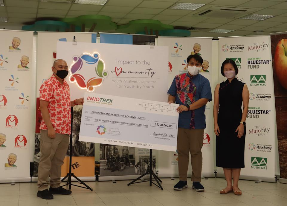 """Tony Tan (left), CEO of Innotrek, presents a cheque of $250,000 for the """"Impact to the Community by Youth"""" grant to Delane Lim, co-Founder and executive director of CLA, in the presence of Gan Siow Huang, Minister of State for Education and Manpower. (PHOTO: Character and Leadership Academy)"""