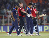 England's Jonny Bairstow, second left, and teammate Dawid Malan, right, walk off the field with Indian players after winning the first Twenty20 cricket match between India and England at Narendra Modi Stadium in Ahmedabad, India, Friday, March 12, 2021. (AP Photo/Aijaz Rahi)