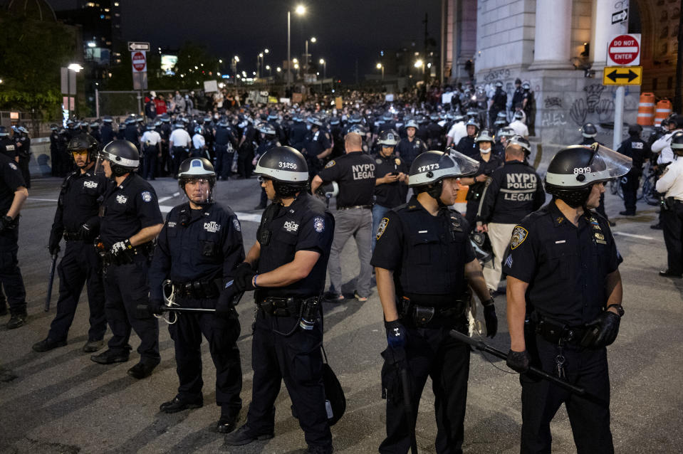 New York police block protesters and activists crossing the Manhattan Bridge from entering the borough Tuesday, June 2, 2020, in New York. An 8 p.m. curfew was imposed following unrest on recent nights. (AP Photo/Craig Ruttle)