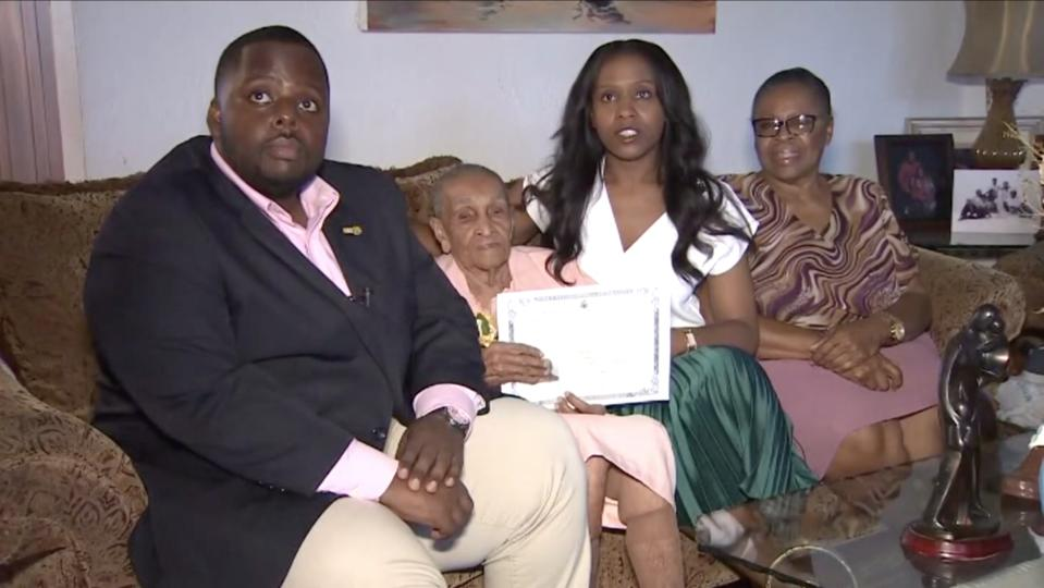 Andrea Joseph holds her certificate of citizenship while seated next to her family including her great-grand nephew and her great-granddaughter. (Credit: WIAT News)