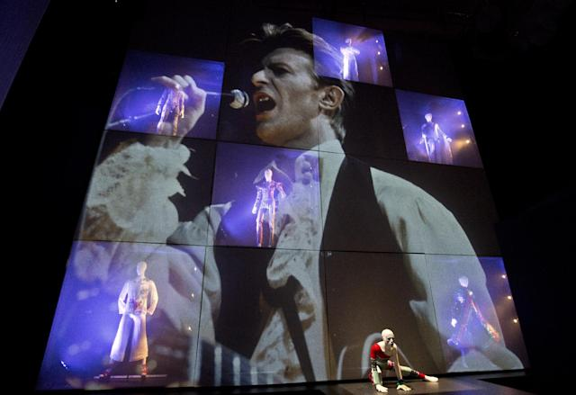 David Bowie appears on a giant screen with various costumes he performed in, as part of a retrospective David Bowie exhibition, entitled David Bowie Is, at the V&A Museum in west London, Wednesday, Mar. 20, 2013, that features 300 objects including handwritten lyrics, original costumes, fashion, photography, film, music videos, set designs and Bowie's own instruments.(Photo by Joel Ryan/Invision/AP)