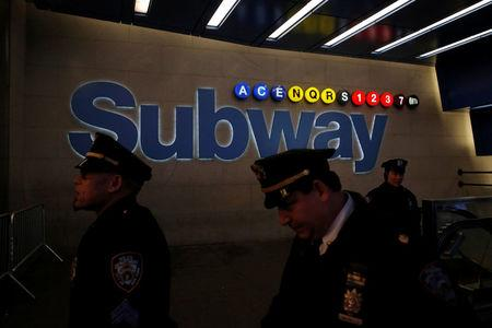 Members of the New York Police Department walk by a subway entrance on 42nd Street following an attempted detonation during the morning rush hour in New York City, New York, U.S., December 11, 2017.  REUTERS/Andrew Kelly