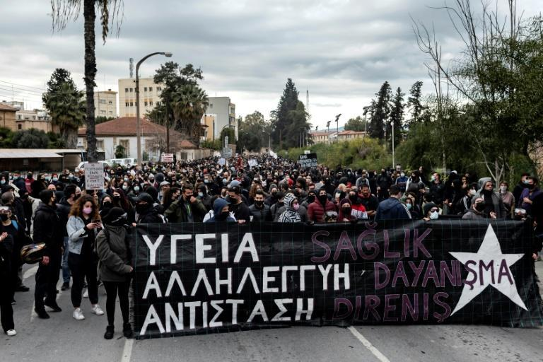 "Protesters march with a banner reading ""Health, Solidarity, Resistance"" during another demonstration in Nicosia on Saturday"
