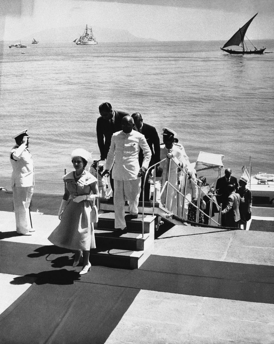 """FILE - In this file photo dated Feb. 26, 1961, Britain's Queen Elizabeth II steps ashore at Bombay, India, for a visit to the atomic energy plant at the """"Gateway to India,"""" which King George V called """"the jewel of the British crown"""" during his 1911 visit. Prince Philip who is accompanying the Queen on the state tour, can be seen nearing top of the Gangplank hat in hand. Prince Philip who died Friday April 9, 2021, aged 99, lived through a tumultuous century of war and upheavals, but he helped forge a period of stability for the British monarchy under his wife, Queen Elizabeth II. Philip helped create the Commonwealth of nations, with the queen at its head, in an attempt to bind Britain and its former colonies together on a more equal footing. (AP Photo, FILE)"""