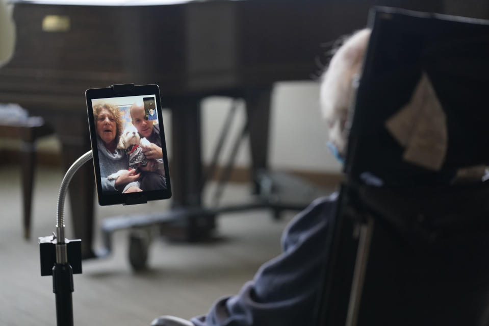 Jerry Woloz, 79, visits with his family and a new dog via a tablet at The Hebrew Home at Riverdale in New York, Wednesday, Dec. 9, 2020. Video and drive-by visits are the only types available at this time due to fears of spreading COVID-19 within the nursing home. New dog recruits are helping to expand the nursing home's pet therapy program, giving residents and staff physical comfort while human visitors are still restricted. (AP Photo/Seth Wenig)