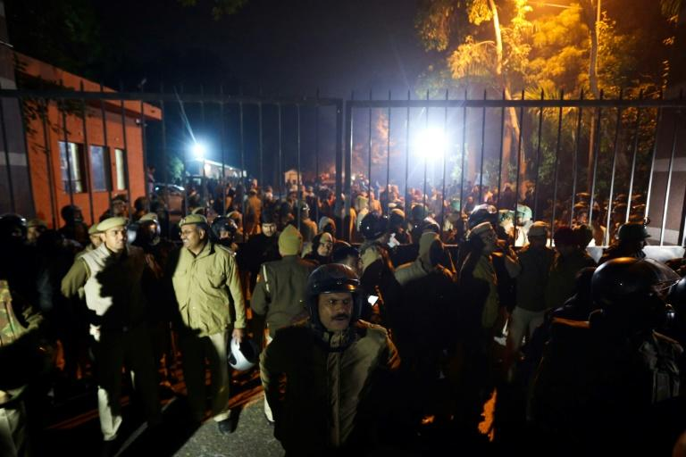 Police gather outside the Jawaharlal Nehru University gate following clashes on campus (AFP Photo/STR)