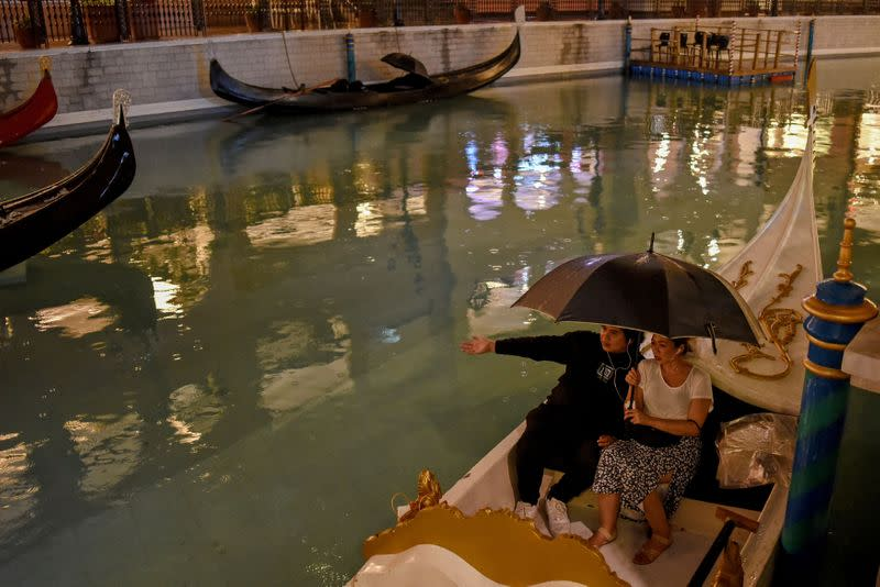 People on a gondola watch a movie while observing social distancing from moviegoers on other gondolas amid coronavirus disease (COVID-19) at a float-in cinema, in Venice Grand Canal Mall, Taguig City, Metro Manila