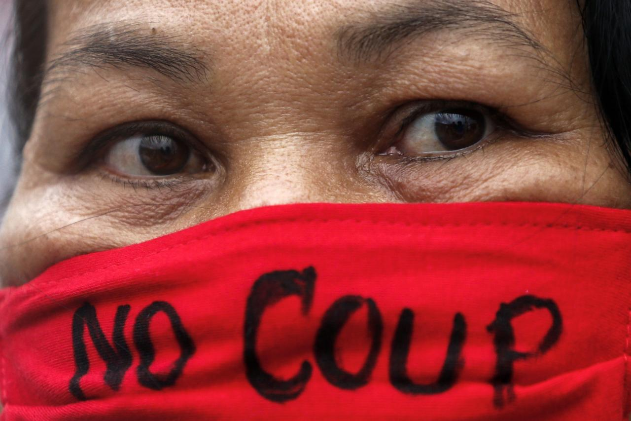 A demonstrator wearing a face mask written with a message takes part in a protest against military rule at Victory Monument in central Bangkok May 27, 2014. Thailand's military rulers settled down to work at their Bangkok headquarters on Tuesday, firmly in charge with royal endorsement while rounding up critics and searching for weapons they fear could still be used to fight their takeover. REUTERS/Athit Perawongmetha (THAILAND - Tags: POLITICS CIVIL UNREST)