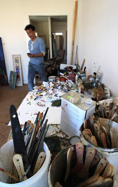 """In this April 18, 2012, photo, Navajo artist Tony Abeyta walks past a table covered with brushes and paints in his studio in Santa Fe, N.M. The 46-year-old painter and jewelry designer is being honored as a """"living treasure"""" as part of this year's Native Treasures Indian Arts Festival, which marks the start of Santa Fe's summer art season. The festival opens on May 25. (AP Photo/Susan Montoya Bryan)"""