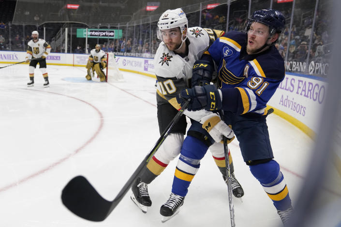 St. Louis Blues' Vladimir Tarasenko, right, gets tangled up with Vegas Golden Knights' Nicolas Roy (10) during the second period of an NHL hockey game Wednesday, April 7, 2021, in St. Louis. (AP Photo/Jeff Roberson)