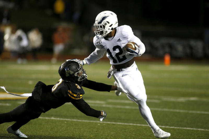 Georgia Southern running back Wesley Kennedy III (12) gets pressure from Appalachian State defensive back Shaun Jolly (3) during the first half of an NCAA college football game Thursday, Oct. 31, 2019, in Boone, N.C. (AP Photo/Brian Blanco)