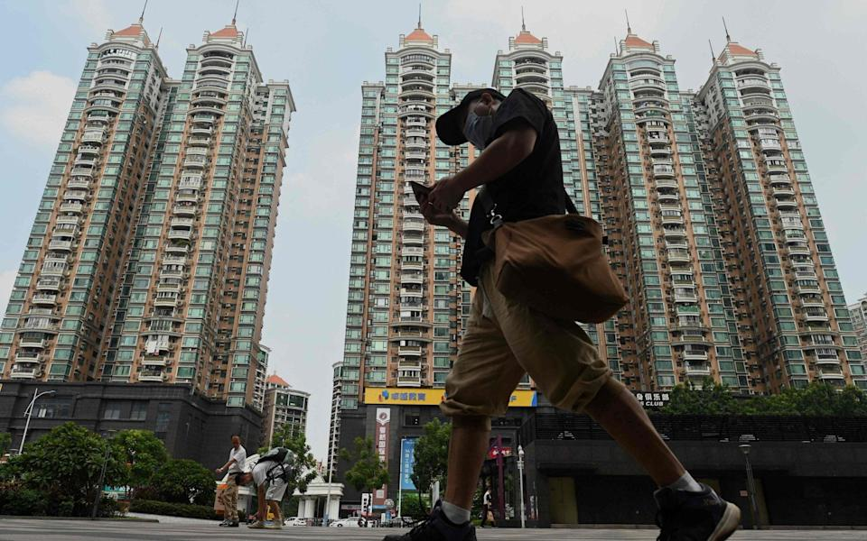A man walks past a housing complex by Chinese property developer Evergrande in Guangzhou, China's southern Guangdong province - NOEL CELIS/AFP