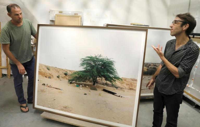"Art photographer Ron Amir (L) and curator Noam Gal flank a picture from ""Somewhere in the Desert"" at the Israel Museum storage room in Jerusalem. The show moves to Paris in September"
