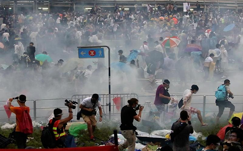 Pro-democracy demonstrators disperse after police fired tear gas near the Hong Kong government headquarters on September 28, 2014
