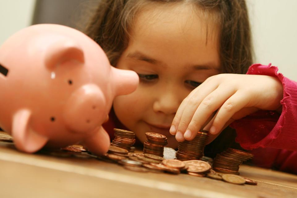 A child with a piggy bank (PA Archive)