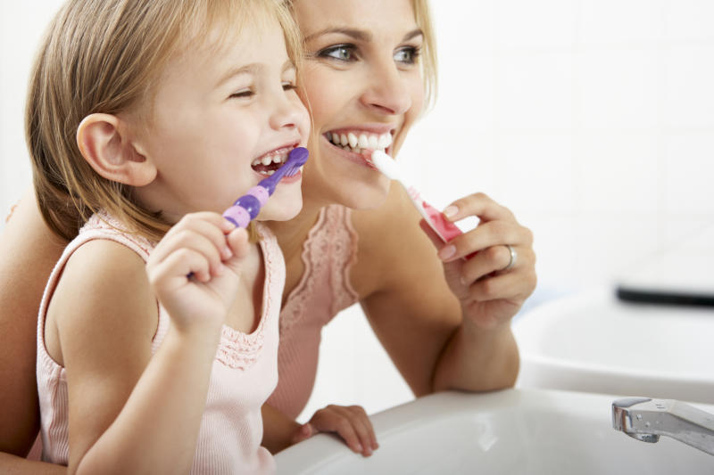 A woman and a child brushing their teeth.