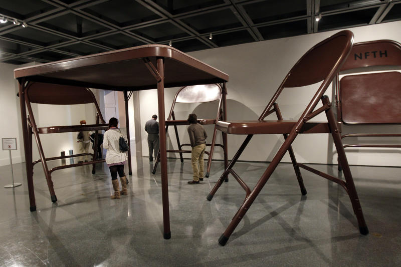"""In this Wednesday, Nov. 14, 2012 photo, giant folding tables and chairs are part of the untitled installation by artist Robert Therrien on display at the New Orleans Museum of Art, in New Orleans, Wednesday, Nov. 14, 2012. The installation is part of """"Lifelike,"""" a traveling exhibit at the New Orleans Museum of Art through Jan. 27. (AP Photo/Gerald Herbert)"""