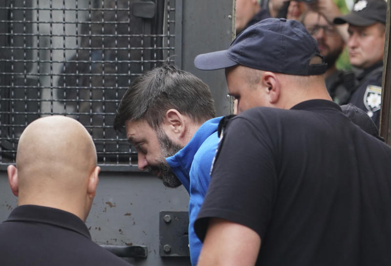 Kirill Vyshinskiy, the head of the Ukrainian office of Russia's RIA Novosti news agency in Ukraine, is escorted from a court room in Kiev, Ukraine, Monday, July 15, 2019. The Ukrainian Prosecutor General's office said that it is likely that a Russian journalist kept in detention in Ukraine is likely to be released. (AP Photo/Evgeniy Maloletka)