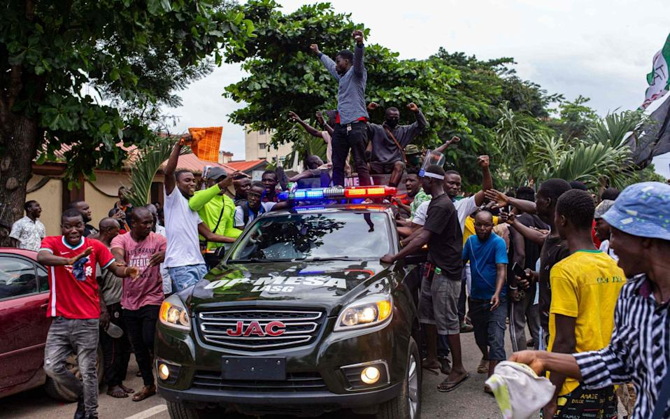 Protesters stand on a vehicle that is part of a military convoy sent to enforce the curfew - BENSON IBEABUCHI/AFP