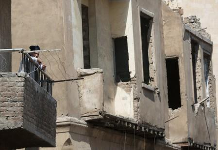 A woman stands in a balcony with old houses in the background at Darb al-Labbana hillside neighbourhood in Cairo