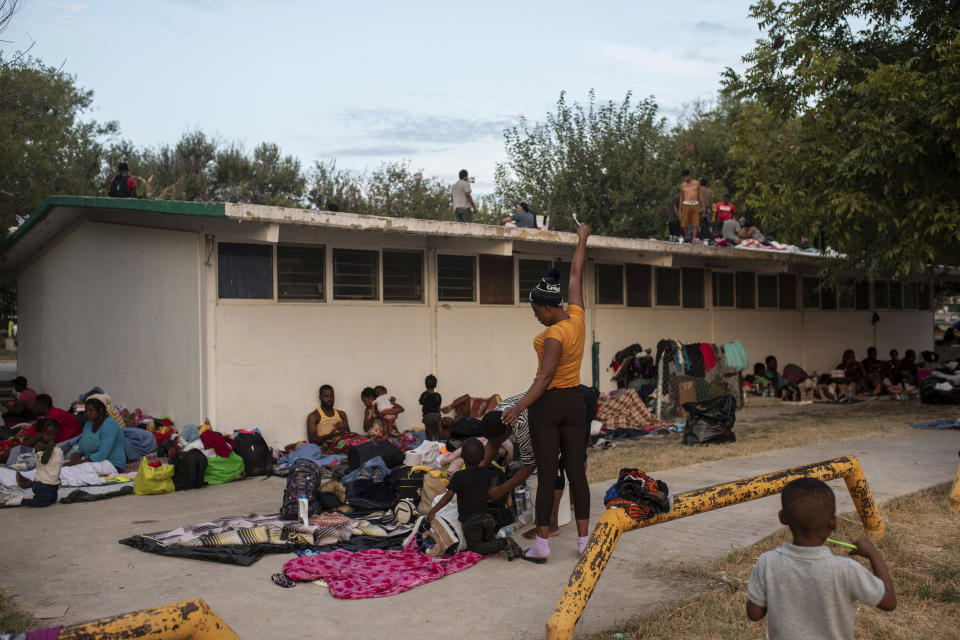 Haitian migrants begin to stir at an encampment at a sports park in Ciudad Acuna, Mexico, Tuesday, Sept. 21, 2021. U.S. authorities have moved to expel many of the migrants who were camped around a bridge in Del Rio, Texas, after crossing from Ciudad Acuna, Mexico. Officials are also trying to to block others from crossing the border from Mexico. (AP Photo/Felix Marquez)