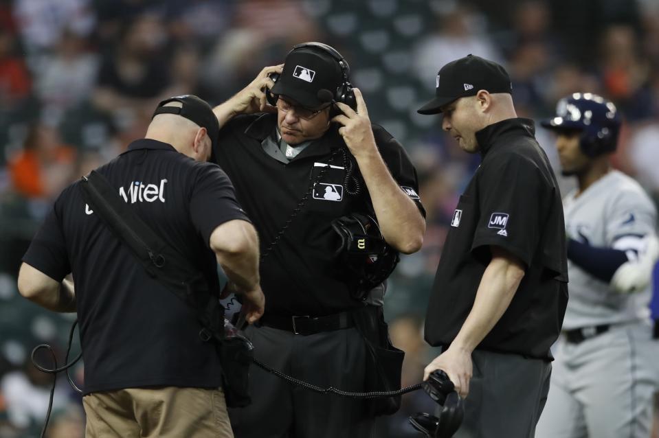 This June 5, 2019 photo shows home plate umpire Paul Emmel and umpire Mike Estabrook reviewing a play during a baseball game between the Detroit Tigers and the Tampa Bay Rays in Detroit. Major League Baseball and its umpires have reached a deal to cover a 2020 pay structure during the coronavirus pandemic, including a 50% cut in May and nothing more this year if no games are played. The sides struck an agreement late Thursday, April 30, 2020 two people told The Associated Press. As part of the deal, MLB has the right not to use instant replays of umpires' decisions during the 2020 season. (AP Photo/Carlos Osorio)