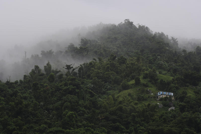 A house without a roof is surrounded by clouds on a mountain in Yabucoa, Puerto Rico, Tuesday, Sept. 24, 2019. Tropical Storm Karen regained strength as it swirled toward Puerto Rico, where it's expected to bring heavy rains and strong winds. (AP Photo/Carlos Giusti)