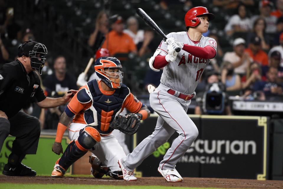 Los Angeles Angels designated hitter Shohei Ohtani, right, hits a solo home run during the first inning of a baseball game against the Houston Astros, Friday, Sept. 10, 2021, in Houston. (AP Photo/Eric Christian Smith)