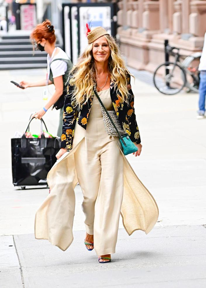 """<p>Carrie Bradshaw's Sarah Jessica Parker looked characteristically trendy and timeless, <a href=""""https://www.instagram.com/p/CRTT6vYDhnX/"""" rel=""""nofollow noopener"""" target=""""_blank"""" data-ylk=""""slk:wearing"""" class=""""link rapid-noclick-resp"""">wearing</a> a vintage Claude Montana paneled linen jumpsuit from Replika Vintage under a statement Dries Van Noten floral silk satin cropped jacket with padded shoulders per the brand's 2017 spring/summer collection. She was additionally seen carrying a vintage Lewis mixed-metal chain bag.</p>"""