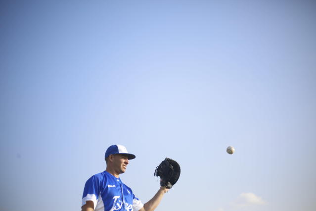 In this Tuesday, Jan. 14, 2020 photo, Danny Valencia catches a ball during Israel's national baseball team practice, in Tel Aviv, Israel. during Israel's national baseball team practice, in Tel Aviv, Israel. As a baseball-crazed kid growing up in Miami, Valencia dreamed of playing in the Major Leagues. The thought of heading to the Olympics, for a foreign country no less, never crossed his mind. But that's the next surreal step for the 35-year-old Valencia, who recently became an Israeli citizen thanks to his Jewishness and is now the star player in Team Israel's improbable run to the Tokyo Games. (AP Photo/Ariel Schalit)