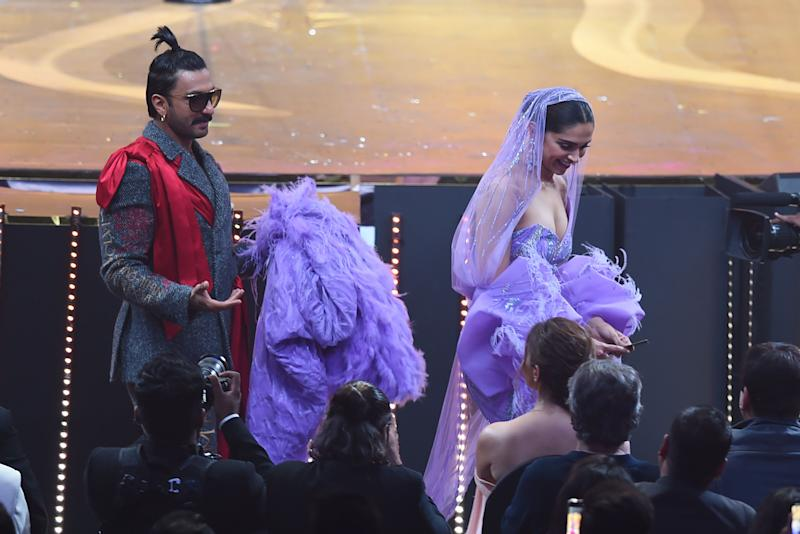 Ranveer Singh carries the back Deepika Padukone's dress during IIFA Awards. (Photo: INDRANIL MUKHERJEE via Getty Images)