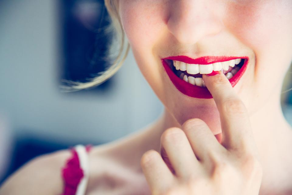 Pretty white woman with red sensual lipstick and colorful nail polish is looking into the mirror, cut out