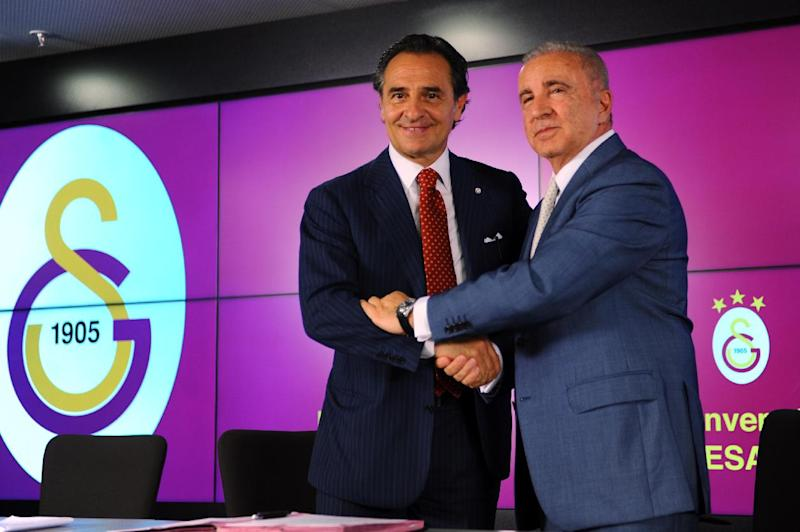 Former Italy football manager Cesare Prandelli (L) shakes hands with Galatasaray football club's president Unal Aysal on July 8, 2014 after signing a new contract with Galatasaray at the TT Arena stadium in Istanbul