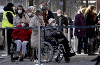 People queue in front of the vaccination center against the COVID -19 disease at the 'Arena Treptow' in Berlin, Germany, Monday, Feb. 1, 2021. Chancellor Angela Merkel and German state governors are going to talk on Monday with representatives of the pharmaceutical industry beefing up the country's sluggish vaccination campaign. (AP Photo/Michael Sohn)