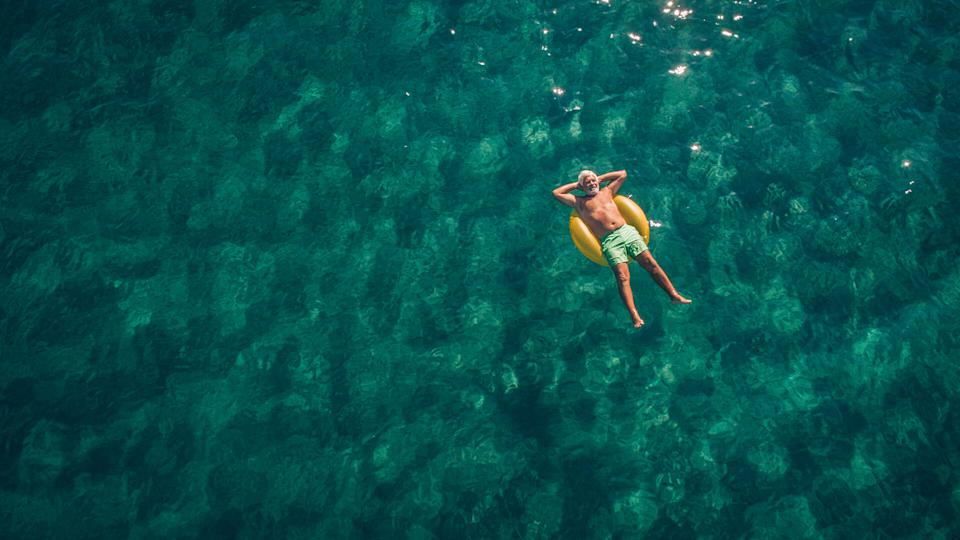 High angle view photo of a senior man relaxing while floating in the ocean using swimming tube; wide photo dimensions.