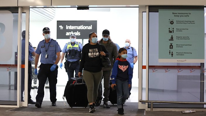 Police at Sydney Airport escort a family arriving from overseas