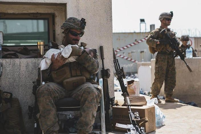 A Marine assigned to the 24th Marine Expeditionary Unit (MEU) calms an infant during an evacuation at Hamid Karzai International Airport, Kabul, Afghanistan, Aug. 20